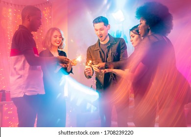 Five young intercultural friends standing in circle and holding sparkling bengal lights in the center while enjoying home party