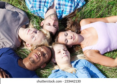 Five young people lying in the grass