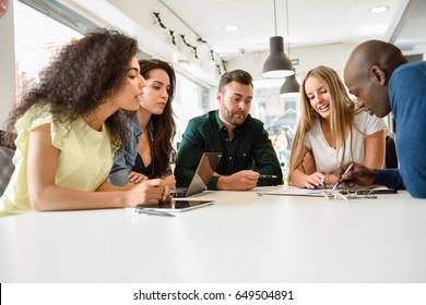 Five young people studying with laptop and tablet computers on white desk. Beautiful girls and guys working together wearing casual clothes. Multi-ethnic group smiling.