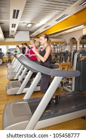 five young people training on treadmills at gym