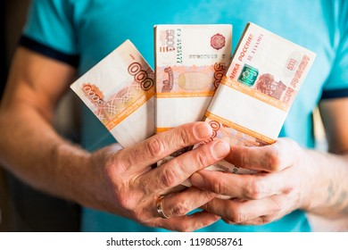 Five-thousandth banknotes of the Russian ruble in a man's hand.male hand with a bundle of banknotes.The isolated denominations of dollars, euro and the Russian rubles in a hand.transfer of money.