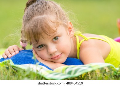 Five-year girl lies on a bed on a green meadow and touching looking to the frame