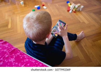 A five-year-old boy in a gray striped pajamas plays a mobile game on a smartphone, sitting on the parquet floor near the bed
