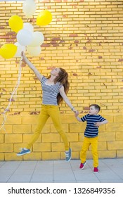 A five-year-old child and his mom in yellow pants and a striped T-shirt plays with balloons against a yellow brick wall. People jumps and rejoices