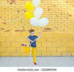 A five-year-old child in yellow pants and a striped T-shirt plays with balloons against a yellow brick wall. The boy jumps and rejoices