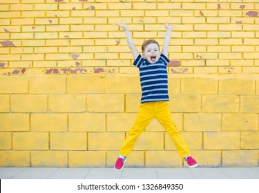A five-year-old child in yellow pants and a striped T-shirt plays against the background of a yellow brick wall.