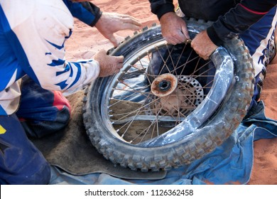 Fix motorbike tyre puncture in the desert, helping hands.