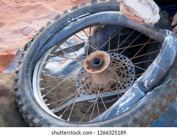 Fix motorbike tyre puncture in the desert with exposed inner tube and talcum powder.