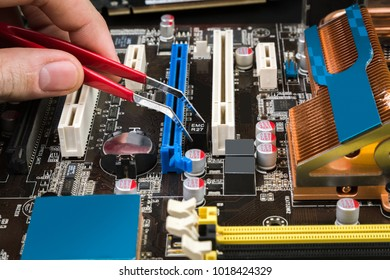 Fix and restore the old game motherboard with tweezers on a black table. Specialist at work