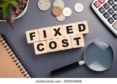 Fixed Cost, text on wood blocks arranged on the desk with a magnifying glass, fixed cost analysis, and reduction concept