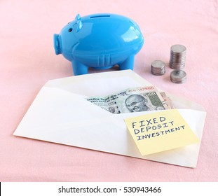 Fixed deposit investment concept, indicated handwritten text on a paper on an envelope with Indian rupees.