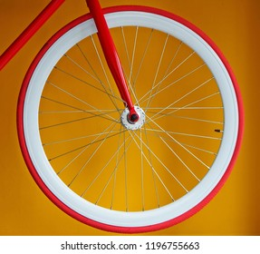 Fixed gear bicycle wheel with thin red tires and white wide rim