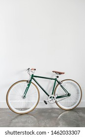 Fixed Green and Brown Bicycle in Modern Home, Fixie Bike inside house, white wall background, isolated retro bicycle