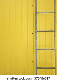 Fixed ladder and yellow metallic sheet wall background.