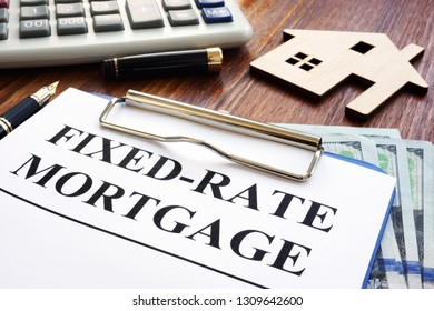 Fixed rate mortgage, wooden home and calculator.