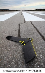 Fixed wing drone laying on its belly on the asphalt surface of an airport track, on a cloudy autumn day