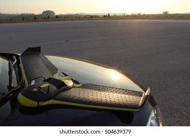 Fixed wing drone laying on its belly on the car hood parked on the airport, cable connected for data transfer. Nice autumn day, close to sunset, sun reflecting on the hood.