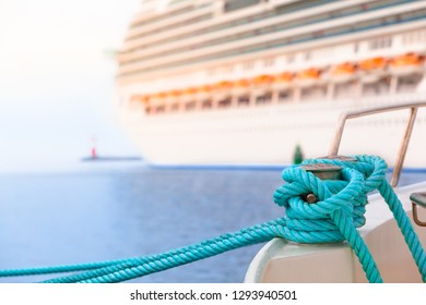 Fixed yacht boat by green rope with knot at bollard in harbor - cruise ship, pier, lighthouse, open sea at background (copy space)