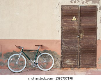 fixie bicycle resting on aged wall