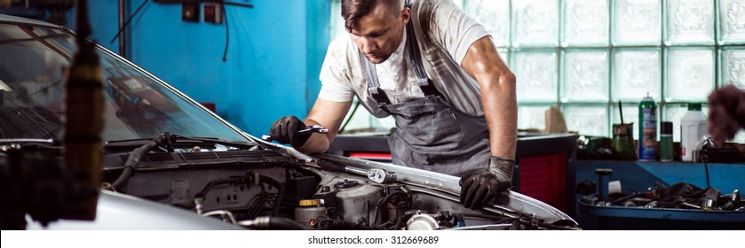 Fixing car engine in automobile repair shop