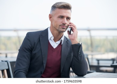 Fixing formal meeting. Handsome man make call in outdoor cafe. Business communication. Serious lawyer in formal style. Formal work fashion. Dress code. Professional attire. Formal and stylish.