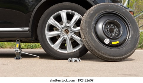 Fixing a puncture at the roadside with a view of the car jacked up with the spare tyre balanced against the side and nuts removed off the wheel