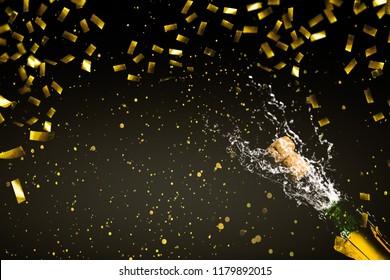 fizzing champagne in rainig gold confetti