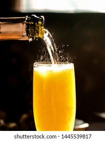 Fizzy pouring close up of champagne mimosa cocktail