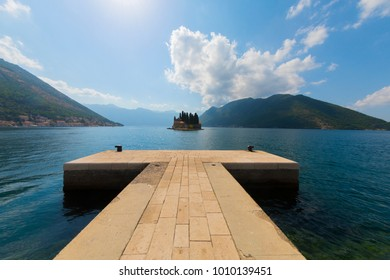 Fjord in Adriatic Sea. Our Lady of the Rock island and Church in Perast on shore of Boka Kotor bay (Boka Kotorska), Montenegro, Europe. Kotor Bay is a UNESCO World Heritage Site