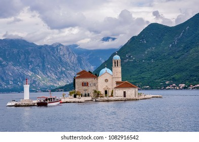 Fjord in Adriatic Sea. Our Lady of the Rock island and Church in Perast on shore of Boka Kotor bay Boka Kotorska , Montenegro, Europe. Kotor Bay is a UNESCO World Heritage Site