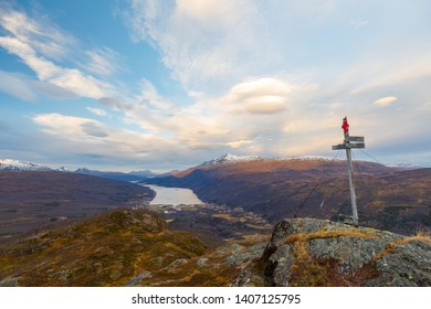 Fjord Gratangen with summit cross and norwegian flag, view from mountain Snolke, sunrise winter