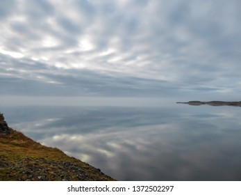 A fjord view. Grass in dried after winter. In the back invisible line of horizon. Skyline blending with the ocean water. Calmness and serenity. Beauty in the nature.