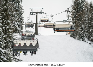 Flachau, Austria - 6.3.2020: Chair lift in Flachau ski resort, Skiers and snowboarders enjoy the ski slopes in Austria Apls winter resort with forest covered in snow on winter season.