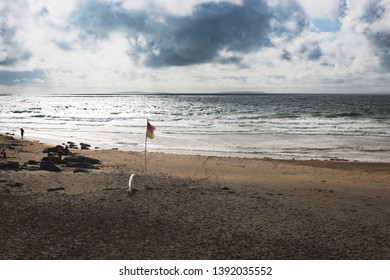 A flag and abandoned surfboard on wild beach in Ireland during summer day with cloudy sku in the background