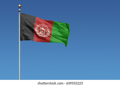 Flag of Afghanistan on pole blowing in wind in front of a clear blue sky