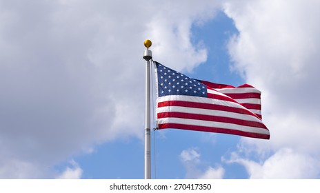 A Flag against a cloudy sky. Symbolizing American Power and industry.