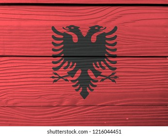 Flag of Albania on wooden wall background. Grunge Albanian flag texture, a red field with the black double-headed eagle in the center.