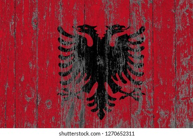 Flag of Albania painted on worn out wooden texture background.