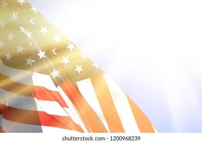flag of America against the blue sky with sun rays