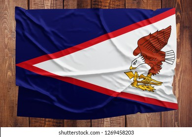 Flag of American Samoa on a wooden table background. Wrinkled Samoan flag top view.