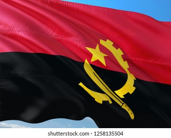 Flag of Angola waving in the wind against deep blue sky. High quality fabric.