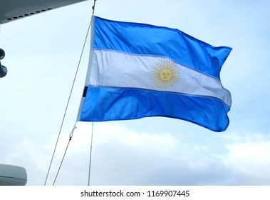 Flag of Argentina of a cruise ship waving against light blue sky