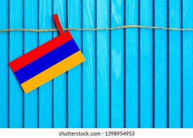 Flag of Armenia hanging on clothesline attached with wooden clothespins on aqua blue wooden background. National day concept.