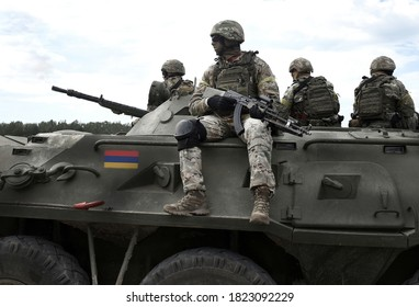 Flag of Armenia on an armored personnel carrier and Soldiers with machine guns. Military Conflict in the Caucasus. Collage.