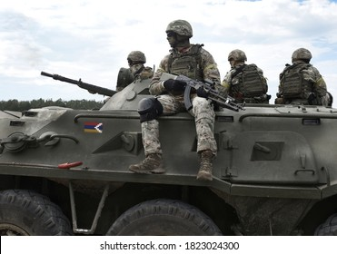Flag of Artsakh and also known as Nagorno-Karabakh Republic on an armored personnel carrier and soldiers with machine guns. Collage.