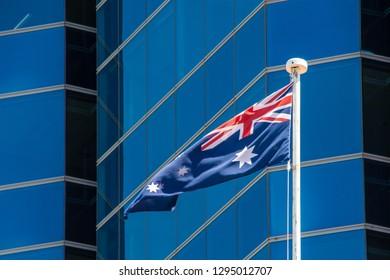Flag of Australia waving in light breeze in front of modern skyscraper