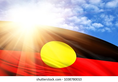 flag of Australian Aboriginal against the blue sky with sun rays