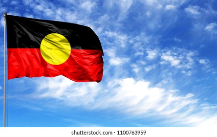 Flag of Australian Aboriginal on flagpole against the blue sky