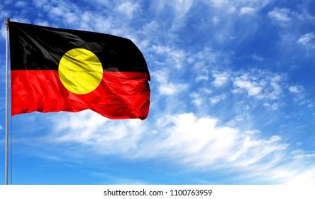 Flag of Australian Aboriginal on flagpole against the blue sky