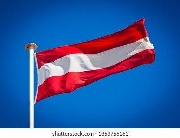 Flag of Austria. Flag blowing in strong wind against pure blue sky. Based on the coat of arms of the Babenberg dynasty, symbol of national patriotism.